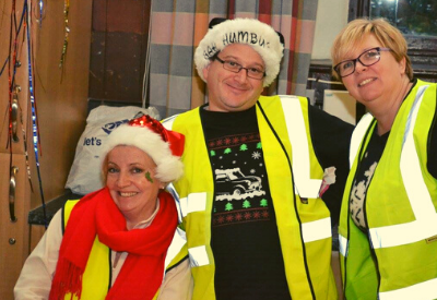 image shows three people in hi-viz waistcoats smiling at the camera. It is Christmas time.