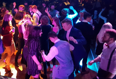 image shows a lot of people dancing at a big party with disco lights.