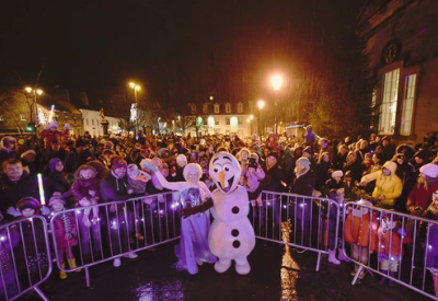 image shows two people dressed as characters from Frozen in the middle of a big crowd, with lots of children at an after dark Christmas event in Haddington