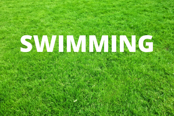Swimming - written in white text on a background of a green lawn