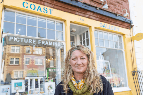 : Image shows Carol Kelly smiling outside her business, Coast Gallery Dunbar.