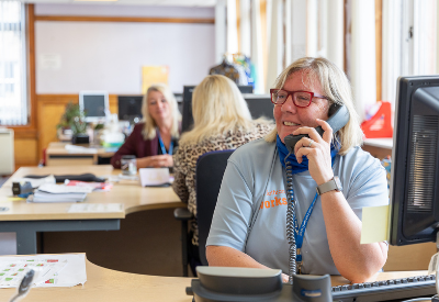Image shows a smiling woman in an East Lothian Works uniform on the phone in a bright and airy office, with two colleagues in the background.