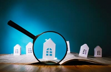 Model houses and magnifying glass (stock image)