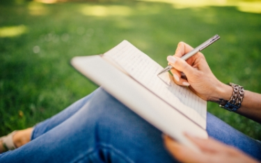 image of a woman sitting outside on grass writing in a book