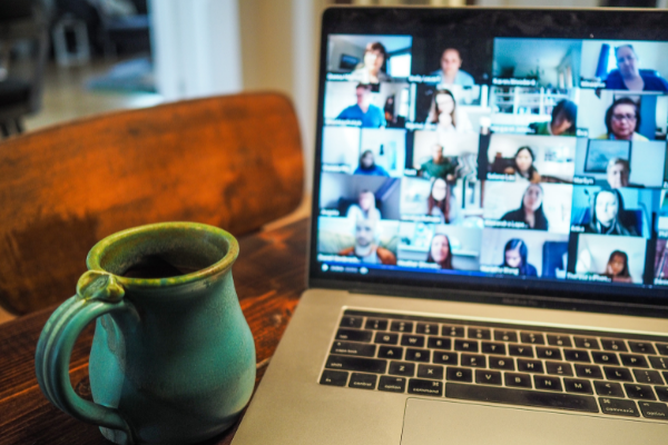 image shows a laptop with a video conference and a coffee mug on the desk next to it.
